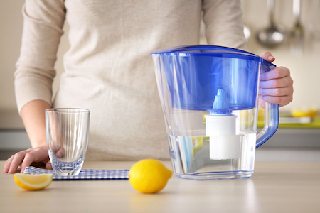 Woman with water filter jug, glass and lemon in the kitchen